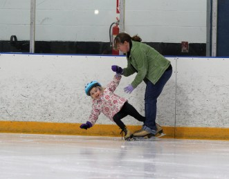 mom helping girl up ice skating
